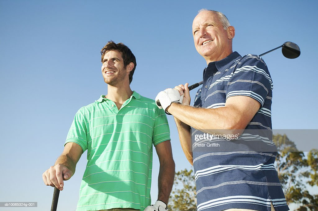 Young man and senior man holding golf clubs outdoors : Foto stock