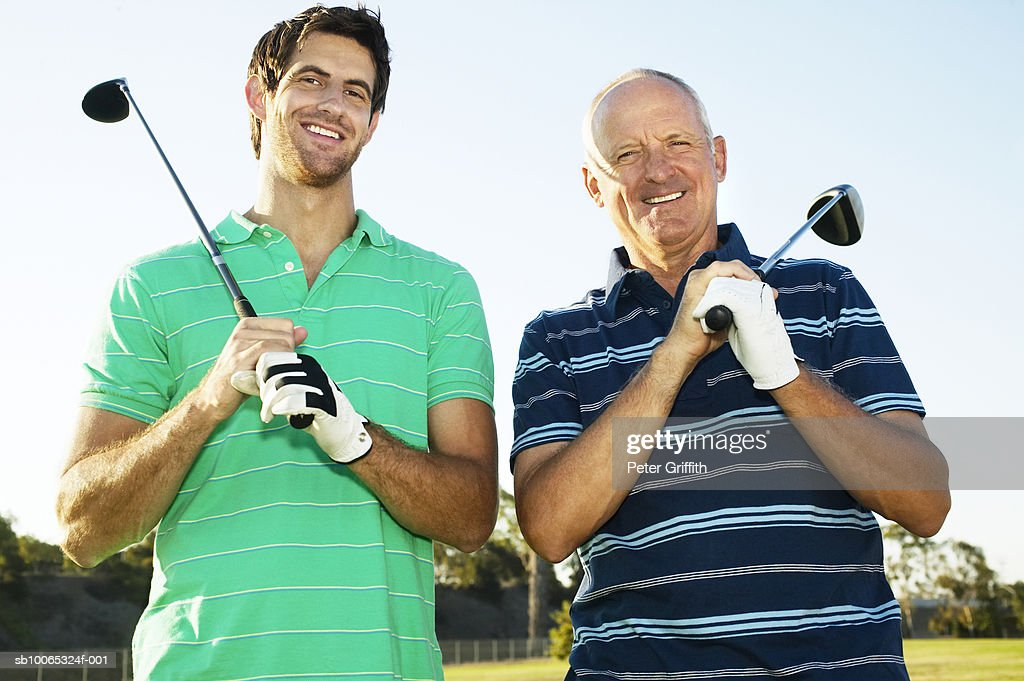 Young man and senior man holding golf clubs outdoors, portrait : Foto stock