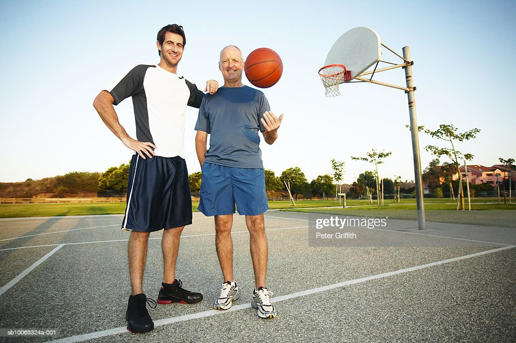 Young man and senior man on outdoor basketball court, portrait : Foto stock