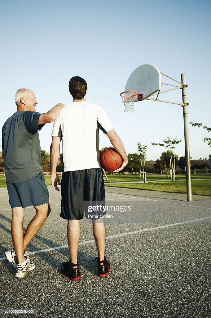 Young man and senior man on outdoor basketball court, rear view : Foto stock