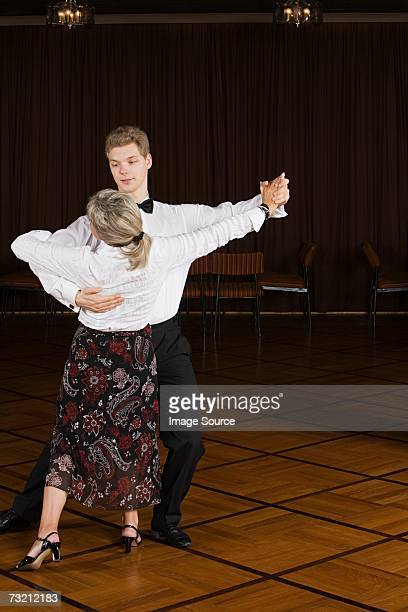 young man and senior woman dancing - ballroom stock pictures, royalty-free photos & images
