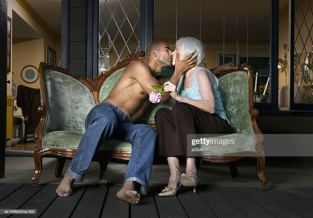 Young man and senior woman kissing on sofa at porch : Foto stock