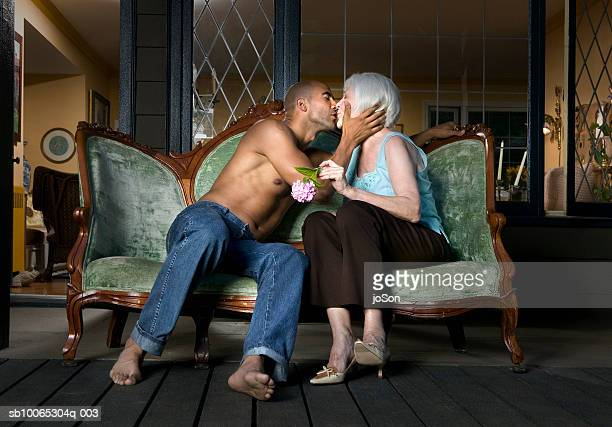 young man and senior woman kissing on sofa at porch - femme cougar photos et images de collection