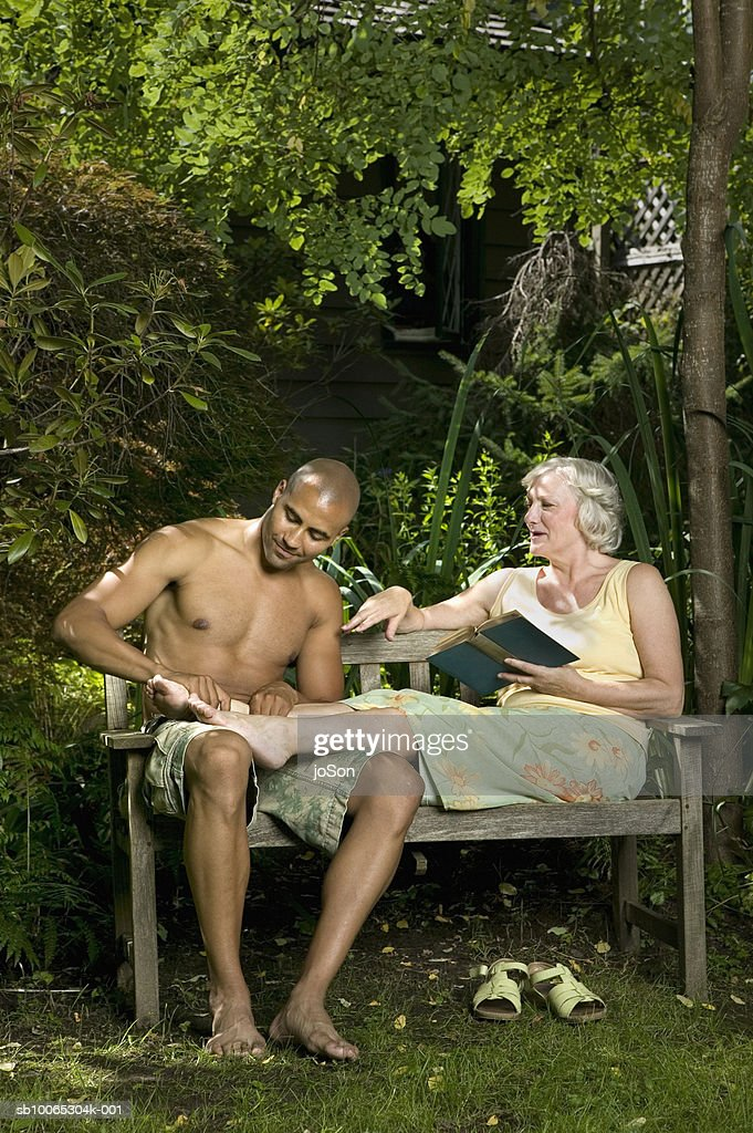 Young man and senior woman sitting on garden bench, man massaging woman's foot : Foto stock