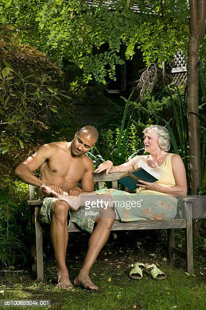 Young man and senior woman sitting on garden bench, man massaging woman's foot