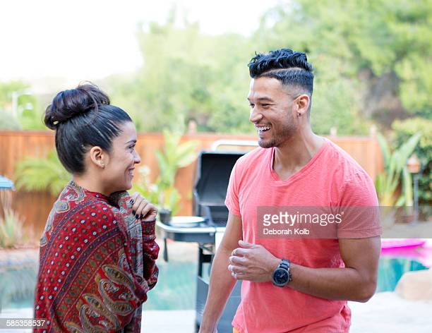 Young man and sister chatting at family barbecue