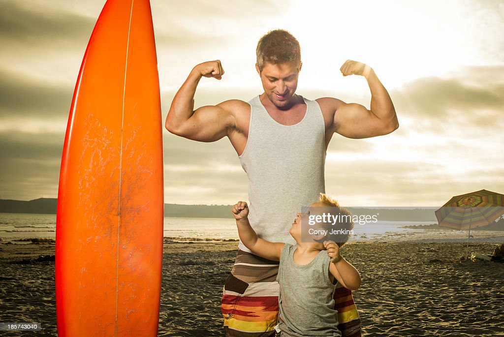 Young man and son flexing muscles on beach : Stock Photo