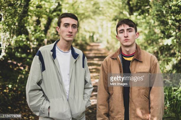 young man and teenage boy with short brown hair wearing casual jackets standing side by side on a forest path, looking at camera. - side by side stock pictures, royalty-free photos & images