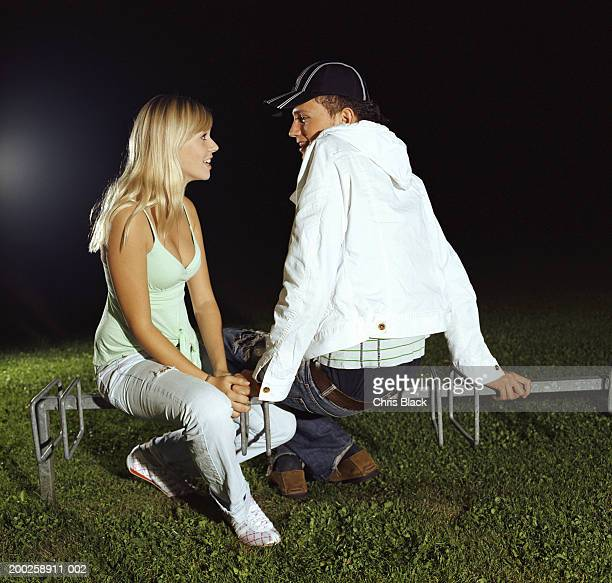 young man and teenage girl (16-18) smiling at each other, outdoors - chav stock photos and pictures