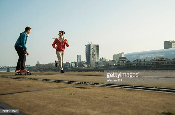 Young man and teenager jogging and skateboarding