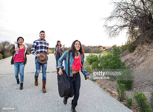 Young man and three adult sisters running along rural road