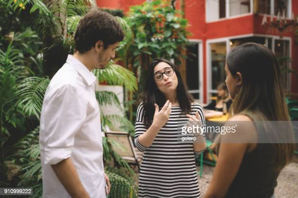 young man and two woman talking on campus - education building stock pictures, royalty-free photos & images