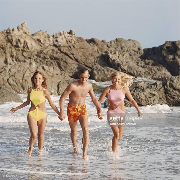 Junger Mann und zwei Frauen Laufen am Strand halten Hände
