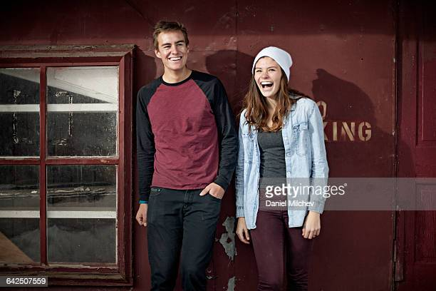 Young man and woman against red building