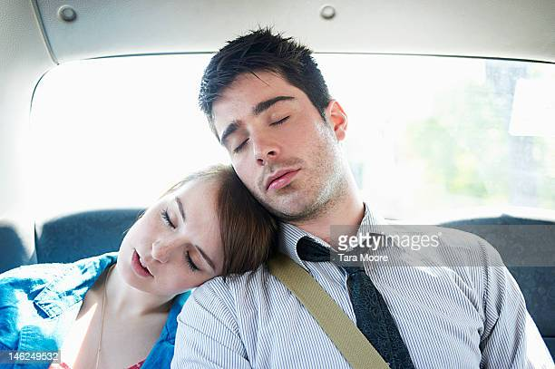 young man and woman asleep in taxi