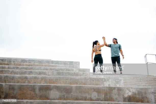young man and woman at top of steps, celebrating workout, south point park, miami beach, florida, usa - celebration fl stock pictures, royalty-free photos & images
