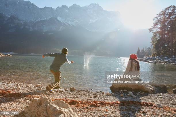 Young man and woman beside lake, young man skimming stones on lake, Garmisch-Partenkirchen, Bavaria, Germany