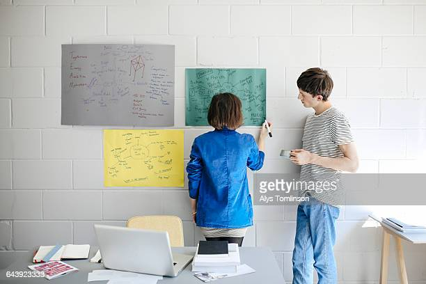 young man and woman brainstorming in studio space