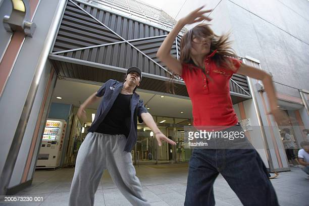 Young man and woman breakdancing at pavement, low angle view