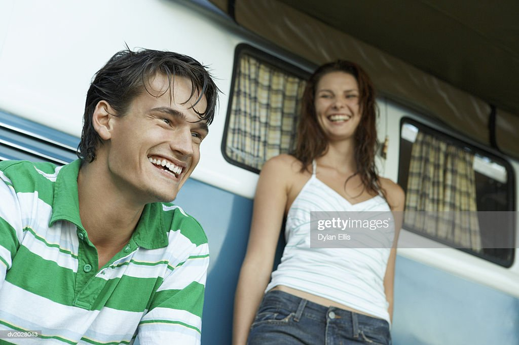 Young Man and Woman by a Motor Home, Laughing : Stock Photo