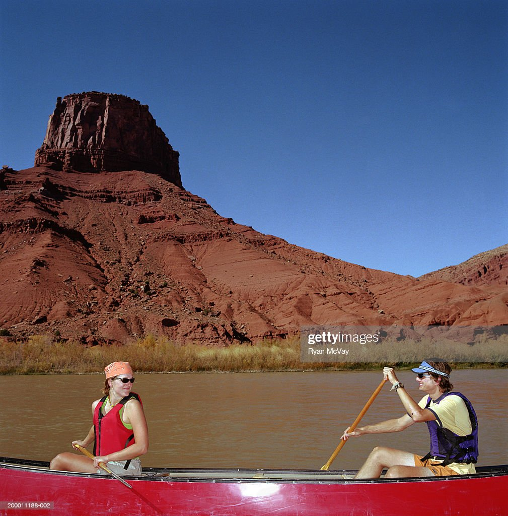 Young Man And Woman Canoeing Side View Moab Utah USA Stock