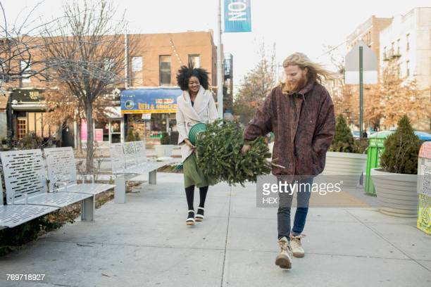 A young man and woman carrying a Christmas tree