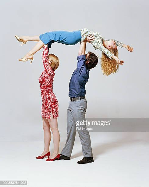 Young man and woman carrying woman over heads, side view