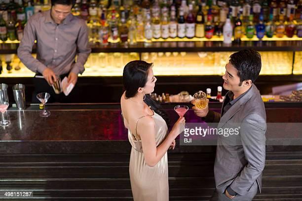 Young man and woman chatting at bar