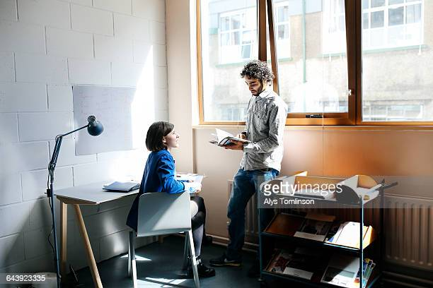 young man and woman chatting in studio workspace