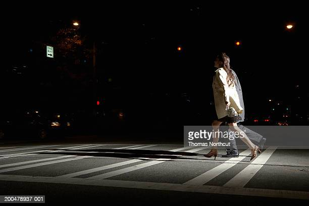Young man and woman crossing street at night, side view
