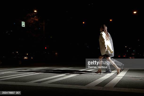 Hombre joven y mujer cruzando la calle en la noche, vista lateral