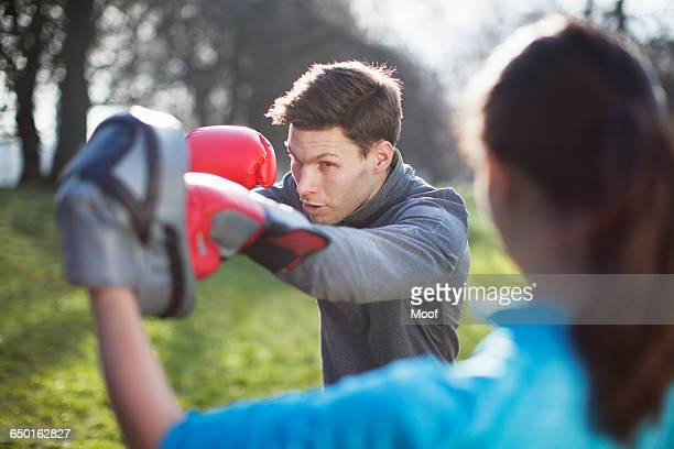 Young man and woman doing boxing training in park