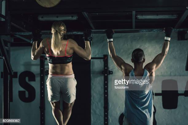 Young man and woman doing chin-ups