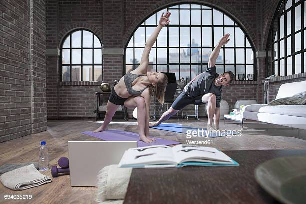 Young man and woman doing yoga exercise in studio