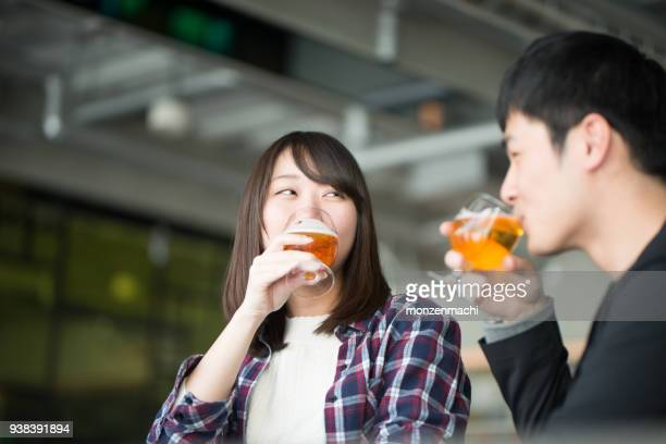 young man and woman drinking beer at happy hour - heterosexual couple stock pictures, royalty-free photos & images