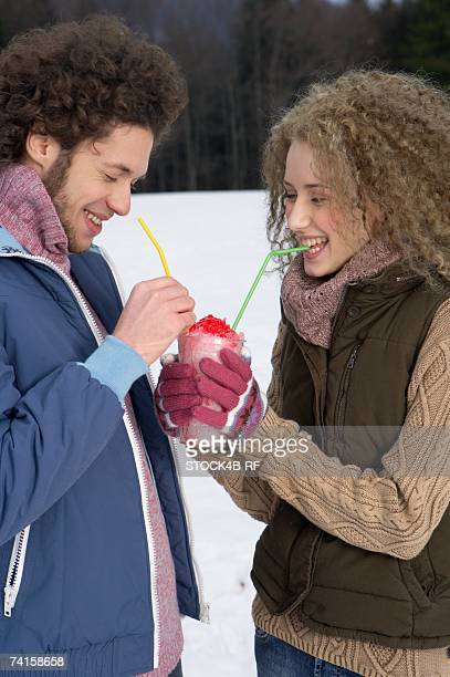 Young man and woman drinking crushed ice of the same beaker, close-up