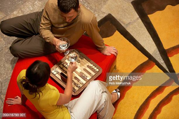 young man and woman drinking martinis and playing backgammon - バックギャモン ストックフォトと画像