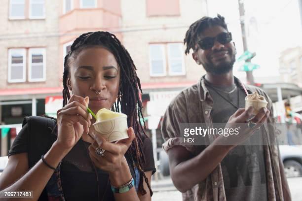 A young man and woman eating frozen yogurt.