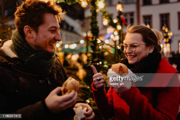 young man and woman eating hot dogs on christmas market - german culture stock pictures, royalty-free photos & images