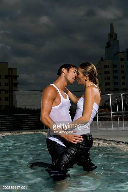 young man and woman embracing and kissing in pool, dusk, side view - wet jeans stock photos and pictures