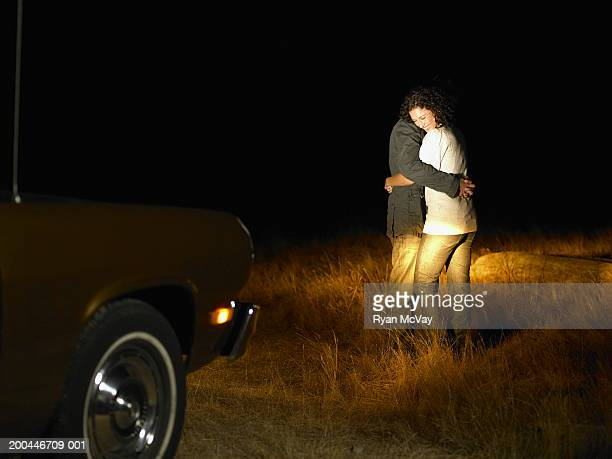 young man and woman embracing in front of parked car, night, side view - vehicle light stock photos and pictures