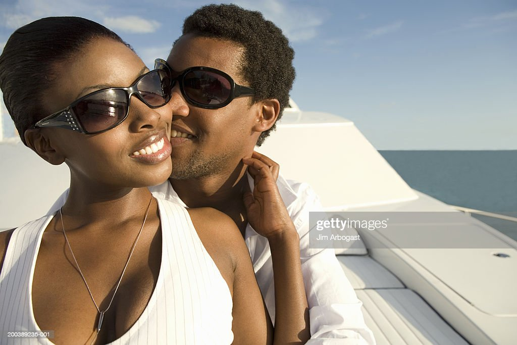 Young man and woman embracing on yacht, smiling : Stock Photo