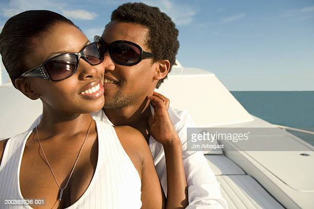 young man and woman embracing on yacht, smiling - chest kissing stock pictures, royalty-free photos & images