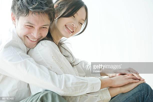 Young man and woman embracing, smiling