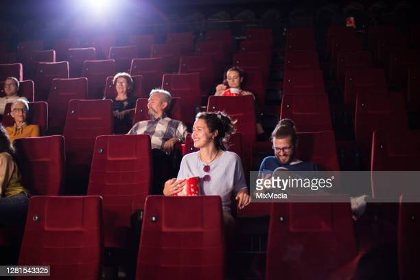 young man and woman enjoying in the cinema - film premiere stock pictures, royalty-free photos & images