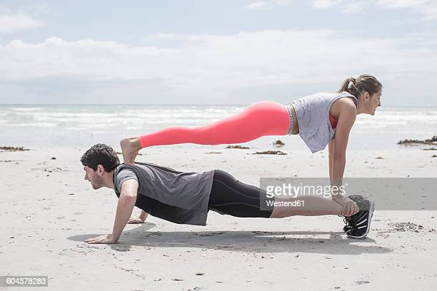 Young man and woman exercising on beach