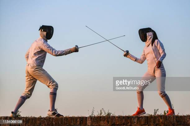 young man and woman fencing - face guard sport stock pictures, royalty-free photos & images