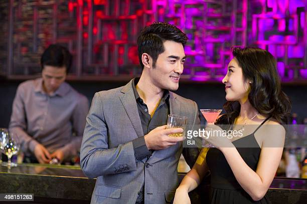 Young man and woman flirting at bar