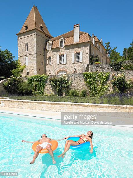 young man and woman floating in pool
