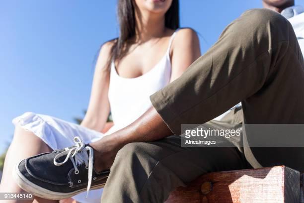Junger Mann und Frau Freunde sitzen auf einer Bank an der Promenade.